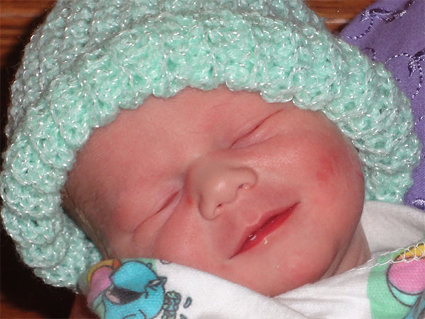 Anne and Keith's newborn baby boy, keplar, wearing light green knitted cap