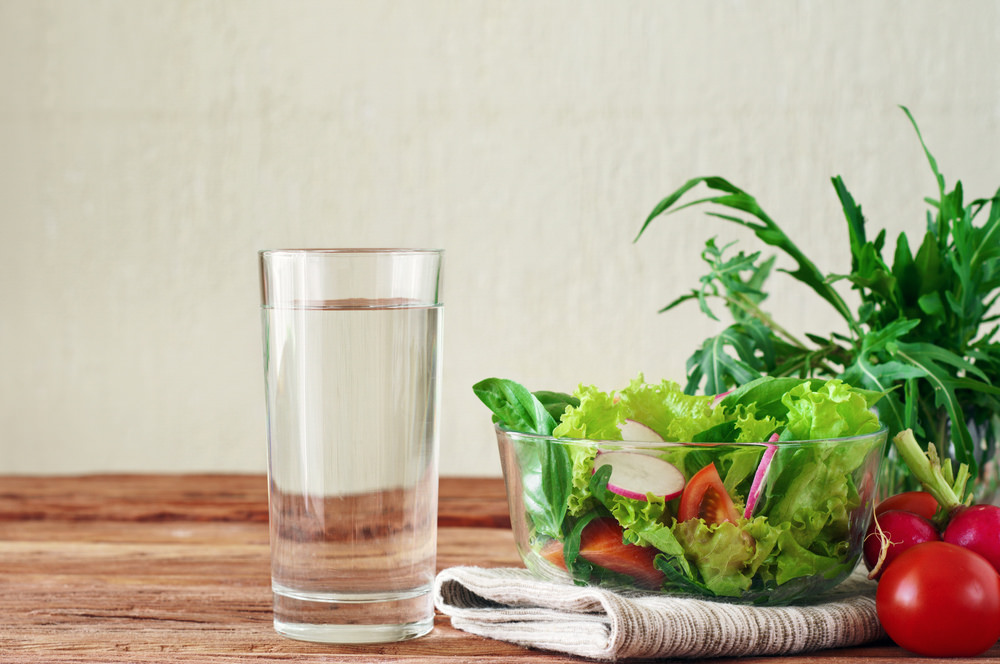 Photo of a glass of water next to a fresh green salad.