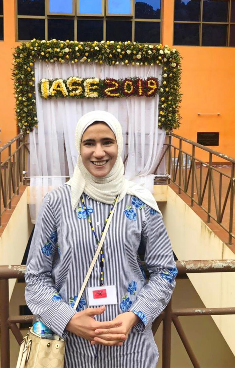 A photo of Roqayah Ajaj standing in front of a conference banner hanging on the wall in a large room and it says IASE 2019, referring to the International Association on Special Education 2019 conference, where this photo was taken. She is looking at the camera and smiling.