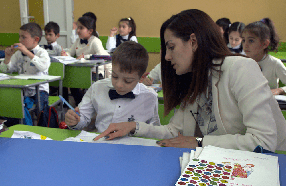 Teacher assists a young student in her classroom in Armenia.