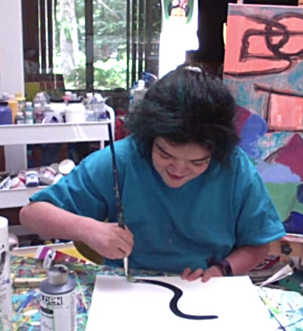 A white woman with black hair looks down at her canvas as she paints in a workshop.