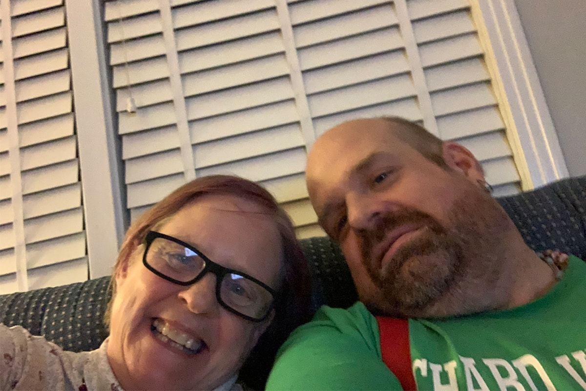 A white woman and her adult son look down at a camera for a selfie. The woman is smiling and wearing dark glasses and the man has a mustache and beard.