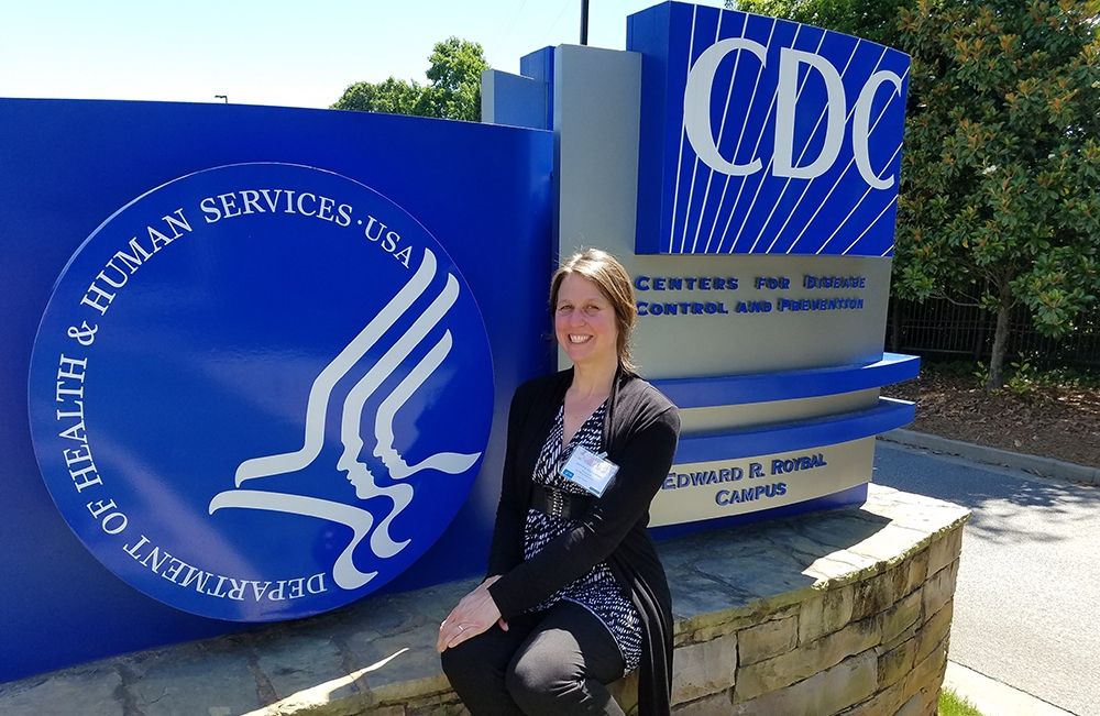 Jennifer Hall-Lande at the entrance sign to CDC headquarters in Atlanta.