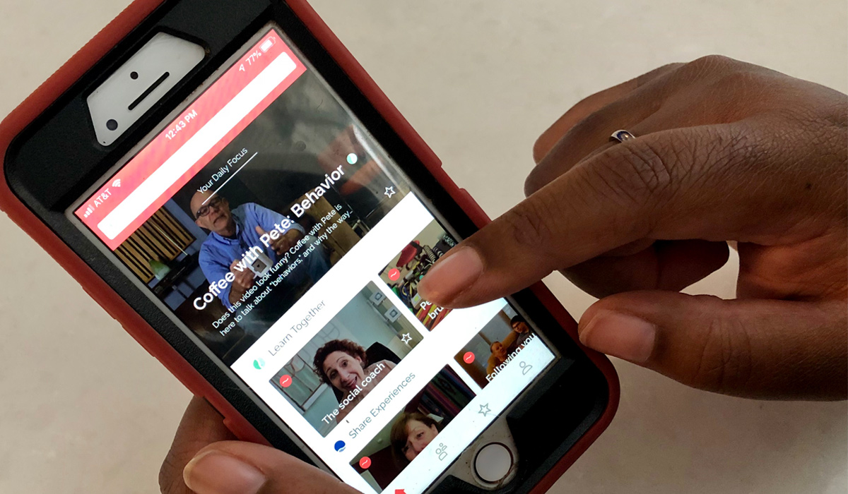 African American woman holding smart phone showing the Quillo website