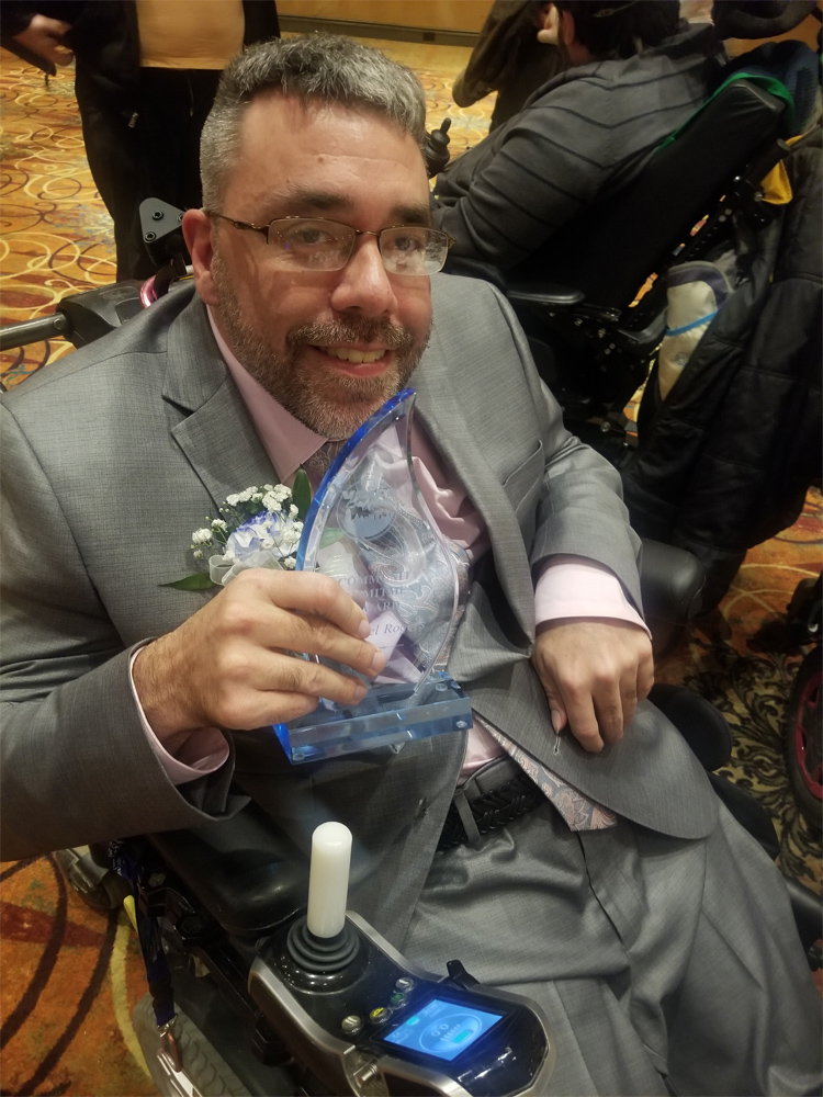 Mike Rogers, of the Self Advocacy Association of New York State, dressed in a formal gray suit and sitting in a wheelchair.
