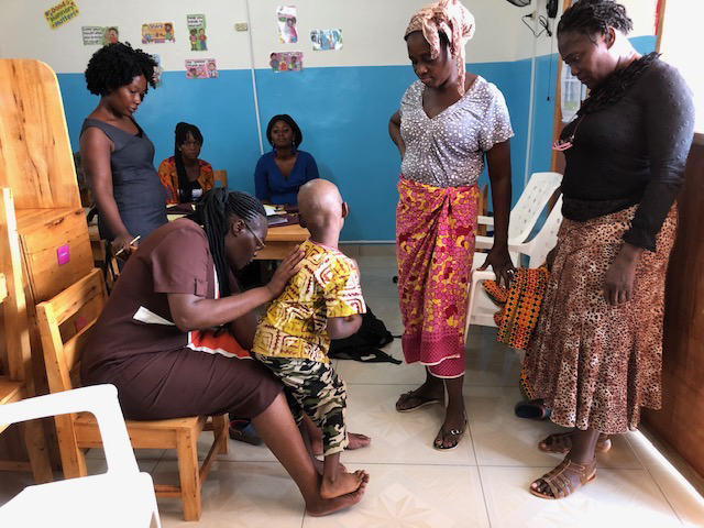 Project consultant Mikala Mukongolwa (seated) is pictured guiding a 6-year-old boy with cerebral palsy, showing his aunt (caregiver) and teachers how to provide physical therapy to help him with balance, coordination, and free movement of his legs.