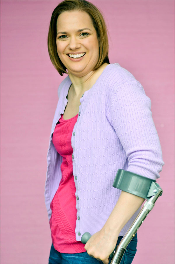 A white woman with straight, blunt-cut hair stands, smiling, with a forearm crutch. She's wearing a bright pink shirt under a lilac cardigan.