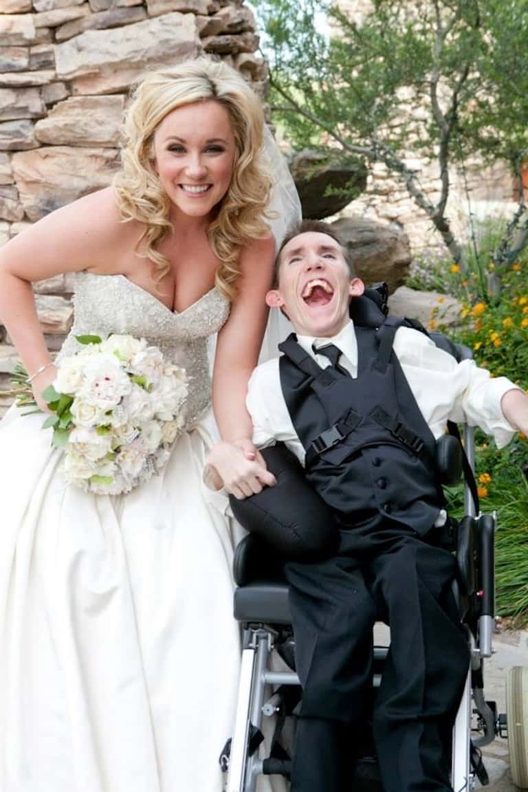Kristin as an adult in her wedding gown holding a bouquet in one hand and holding onto brother Kevin's hand as he sits next to her in his wheelchair. He's wearing a formal black suit, and they're both laughing.