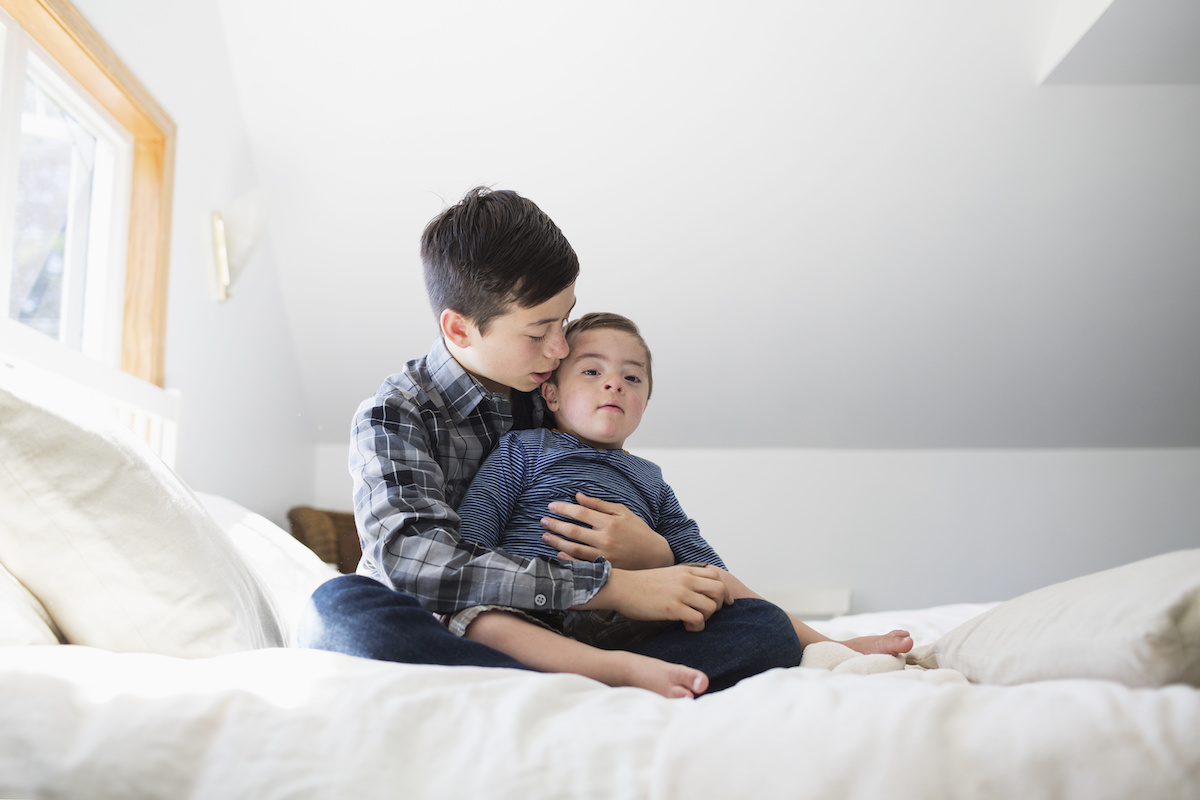 An elementary-school-age boy sitting on a bed and holding his toddler-aged younger brother with Down syndrome in his lap. The older brother is talking or singing to the younger brother.