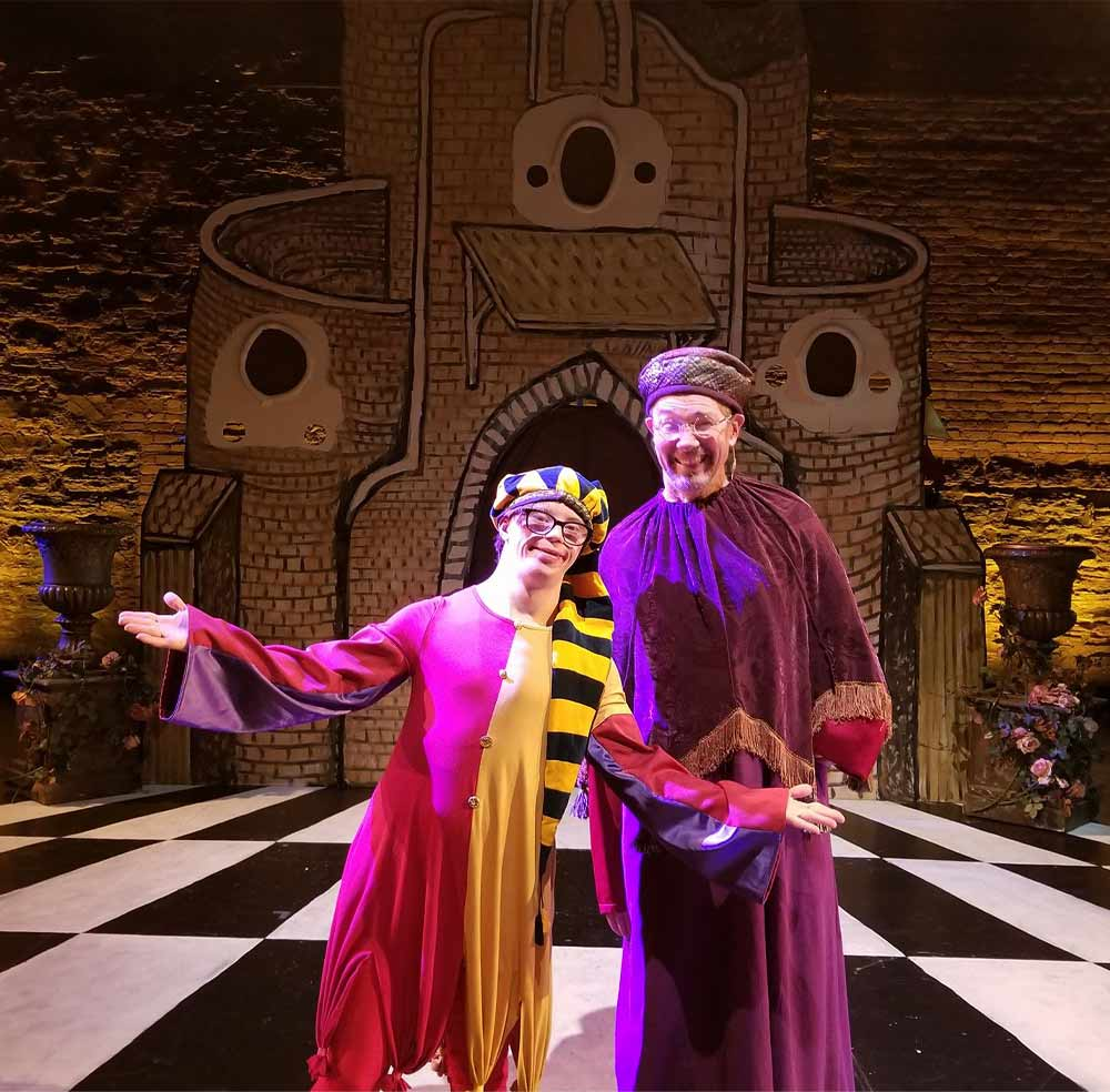 Two white men, both wearing glasses, stand on a stage dressed in brightly colored costumes. The shorter man has outstretched arms and stands in front of the other.