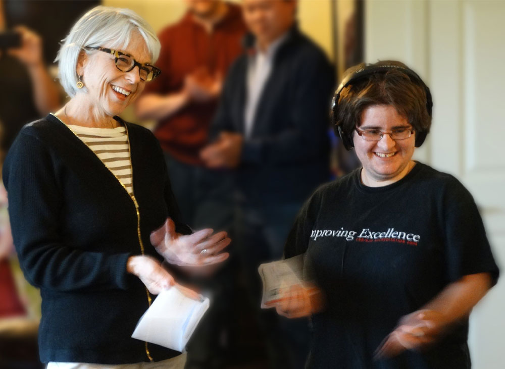A white woman with gray hair and tortoise-shell glasses stands, laughing and clapping her hands. Next to her, a younger woman with short, dark hair and wire-rimming glasses wearing headphones and a black graphic t-shirt, smiles.