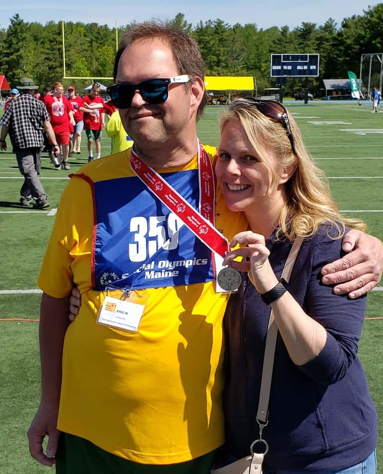 Eric, wearing sunglasses, a sports shirt and racing number, has his arm around his sister, Tonya, who is smiling and holding up a medal that Eric wears around his neck after a Special Olympics event in the state of Maine.