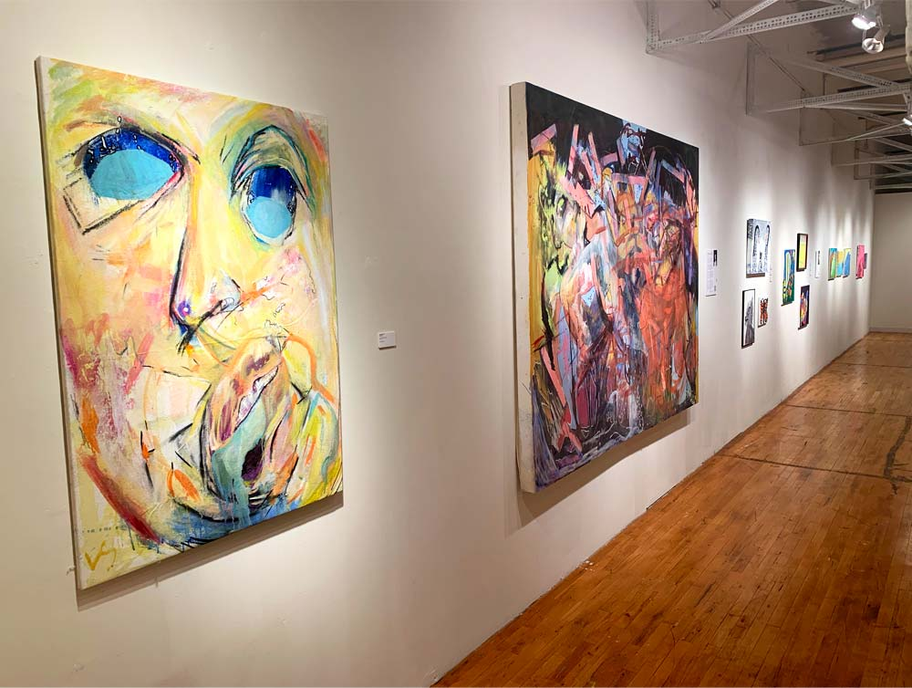 A gallery wall shows several paintings. The first features an abstract face with bold yellow as the dominant color. The second painting a multi-colored abstract. The paintings are against a white wall on hardwood flooring.