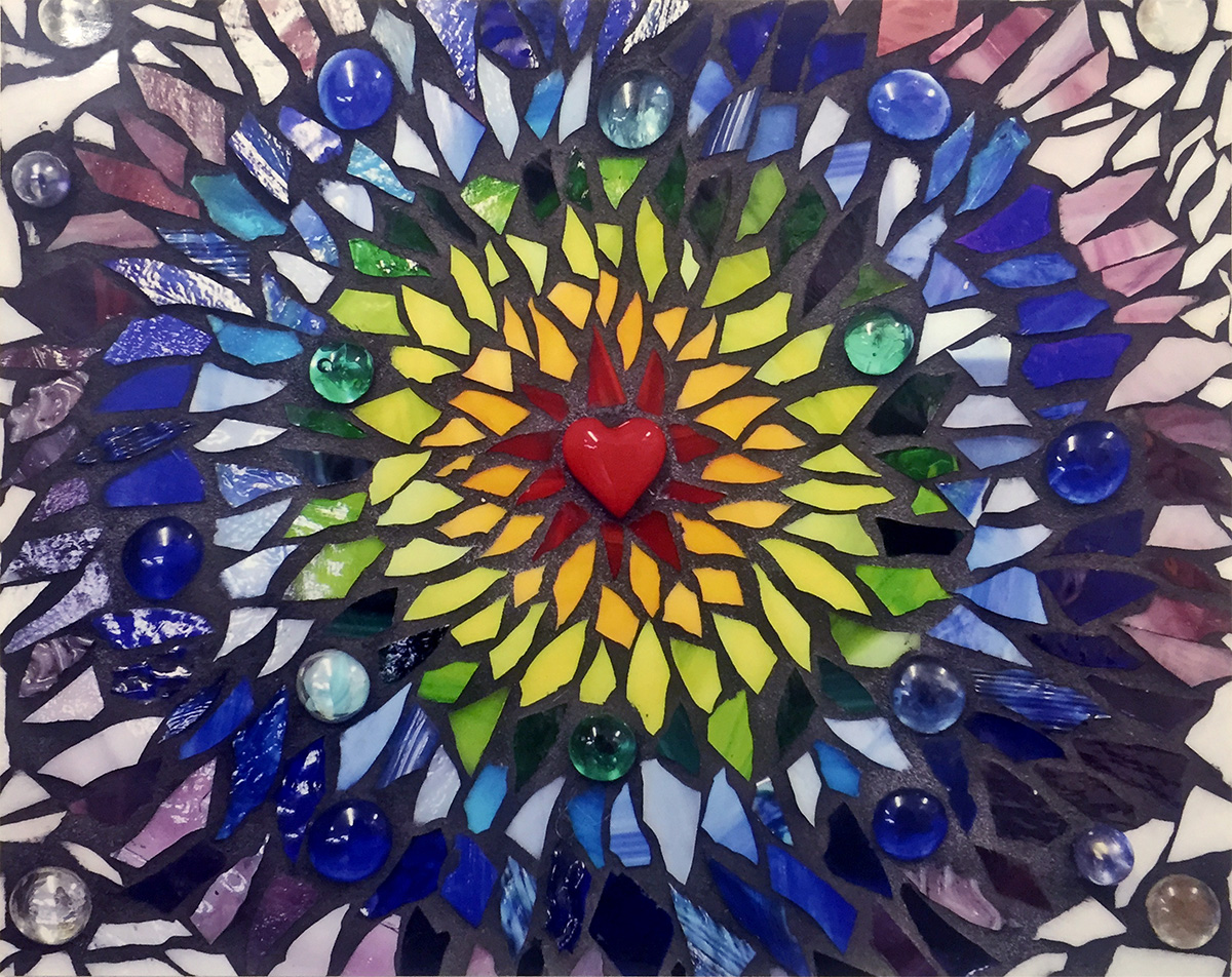 Photo of mosaic of broken glass in the colors of the chakra, red, orange, yellow, green, blue, purple, yellow. Center of art has small red heart made of polished stone.