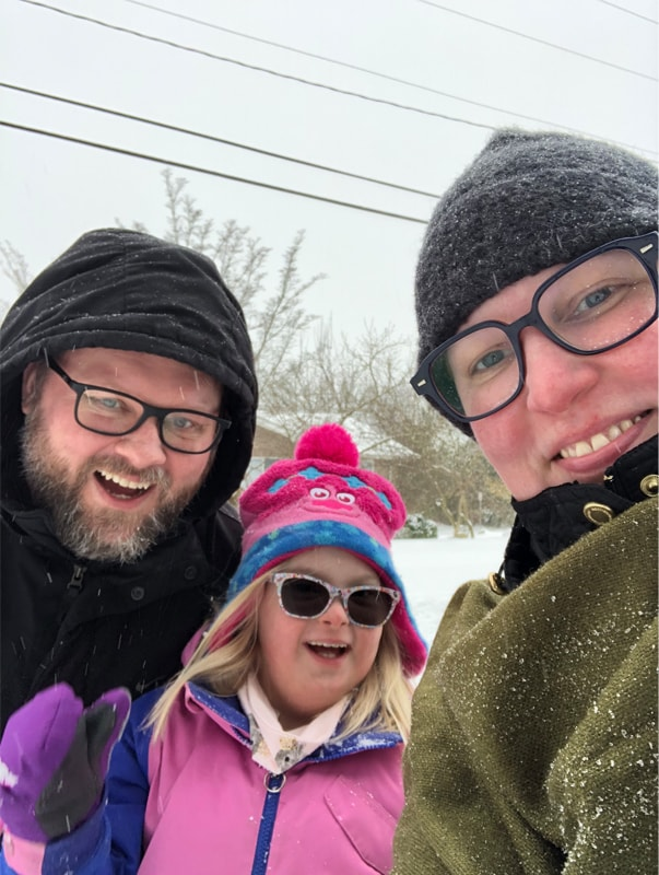 A family dressed in winter clothes huddles close and smiles. A man wearing glasses and a black, hooded winter coat leans into his daughter, who is wearing a pink and blue fuzzy ski hat, a pink winter coat with blue lining and purple mittens. She is smiling and wearing sunglasses. A woman in an olive coat and gray ski hat with snow on it and wearing glasses smiles at the camera.