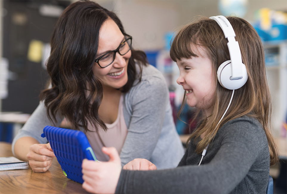 Young student with visual impairment wears headphones as an accommodation while her teacher looks on.