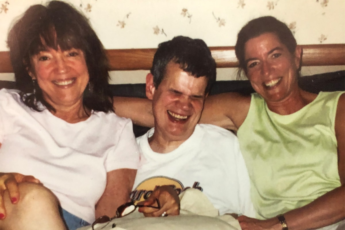 Two women sit with their brother in between them. The women are smiling and the man is laughing with his eyes closed.