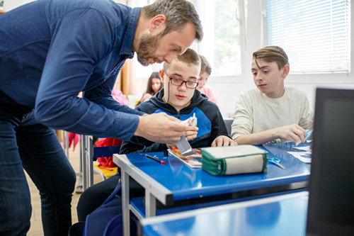 A teacher assists two students who appear to be male with an assignment. The teacher is bent over their desk working intently. One student appears to have a disability.