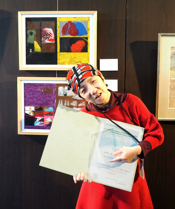 A woman from Hong Kong stands with her diploma, pointing to it and bending slightly to the side. She's wearing a patterned headscarf and a bright red dress and is standing in front of two paintings.