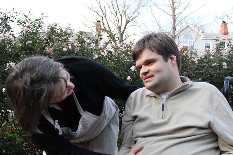 "A close-up photo of Sue Swenson and her son Charlie, about whom she talks in her part of the article, ""The Future of Self-Determination: Four Visions."" He is an adult, seated in a garden and Sue is bending down to speak with him."