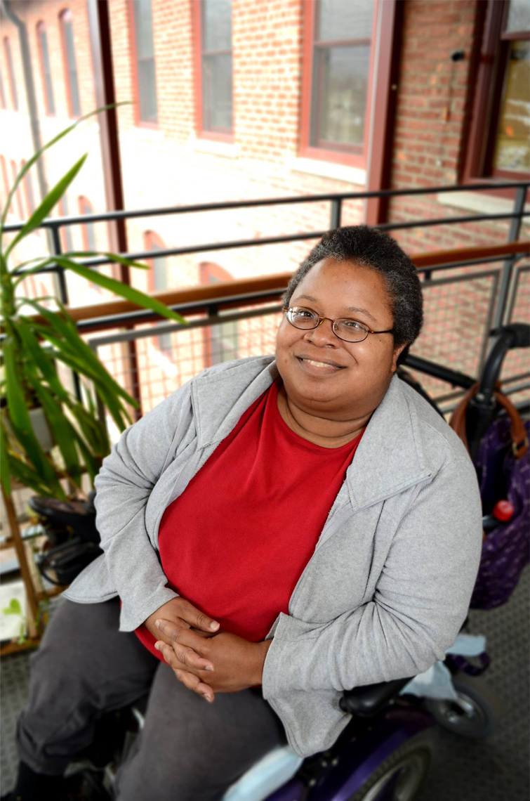 Shameka Andrews, a self-advocate, looks up and smiles at the camera from her wheelchair. She wears glasses, a red shirt, and gray sweater.
