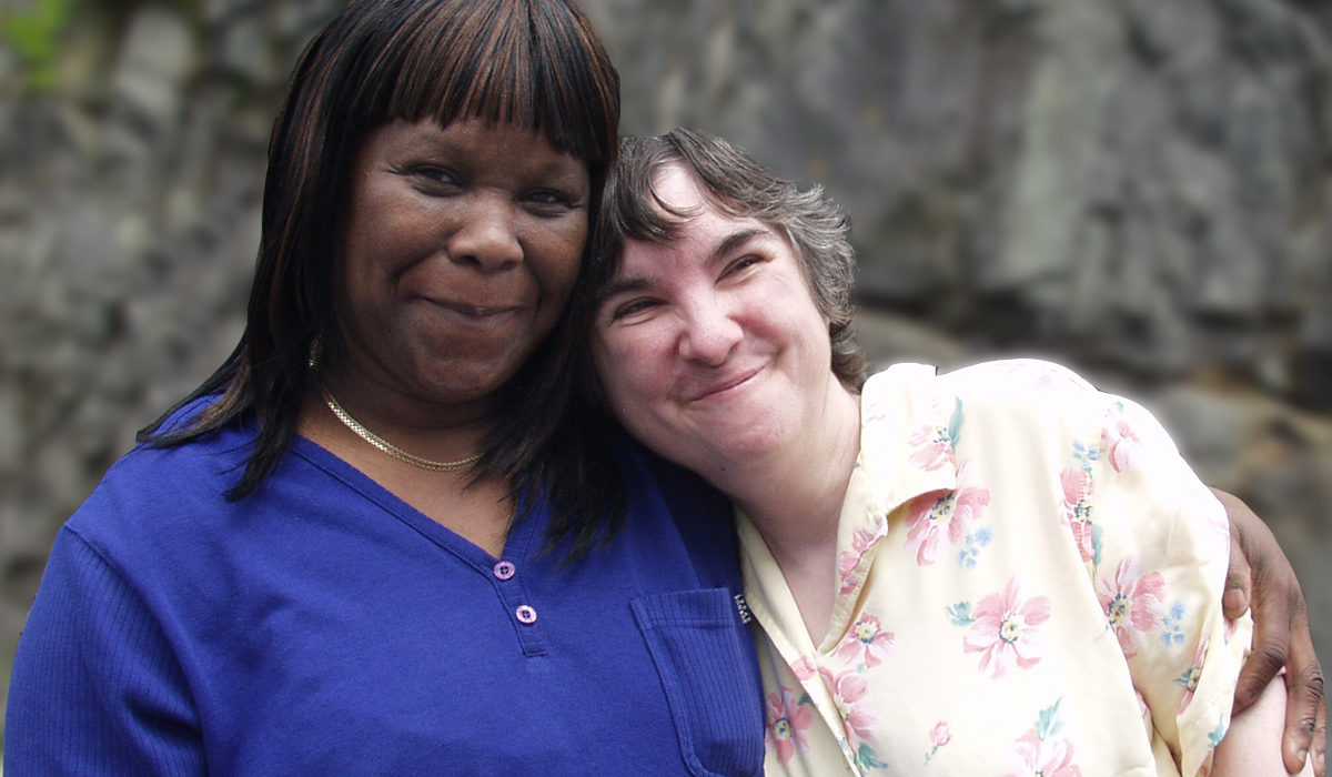 African American woman in blue shirt hugging older white woman with floral shirt.