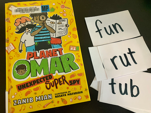 "A book, titled ""Planet Omar Undexpected Super Spy"" Next to it are vocabulary words: fun, rut, and tub."