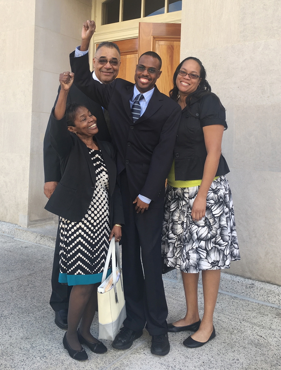 """This photo of the King family accompanies their personal story, """"Our Journey of Supported Decision Making for Ryan."""" The photo is the same one as on the cover of this Impact issue, and it shows Ryan King standing in front of a court building with his mother, father, and sister around him. The men are wearing suits and ties and the women are wearing dresses. They are looking at the camera and smiling broadly, and Ryan and his mother each have their right arms raised in the air in a victory/celebration gesture."""