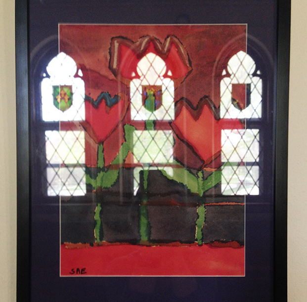 """In the photograph, the cathedral windows are reflected in the picture frame glass of """"Tulips Underwater,"""" a painting by the late Stephanie Evelo."""