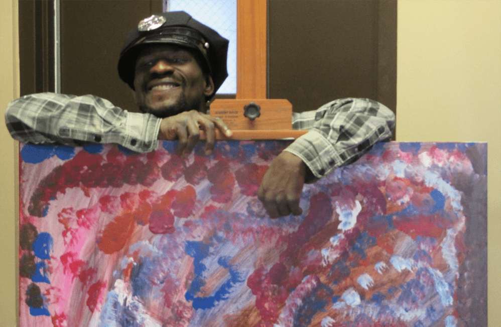 Nymeh T of Partnership Resources Inc. poses with one of his paintings.