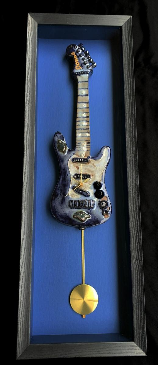 Ceramic 3d blue over white slip & cobalt & black stains guitar floating over museum encased frame with clock mechanisms.