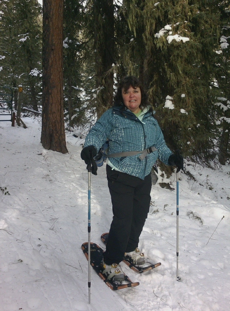 Photo of a caucasian woman in the snow wearing winter clothes using snow shoes.