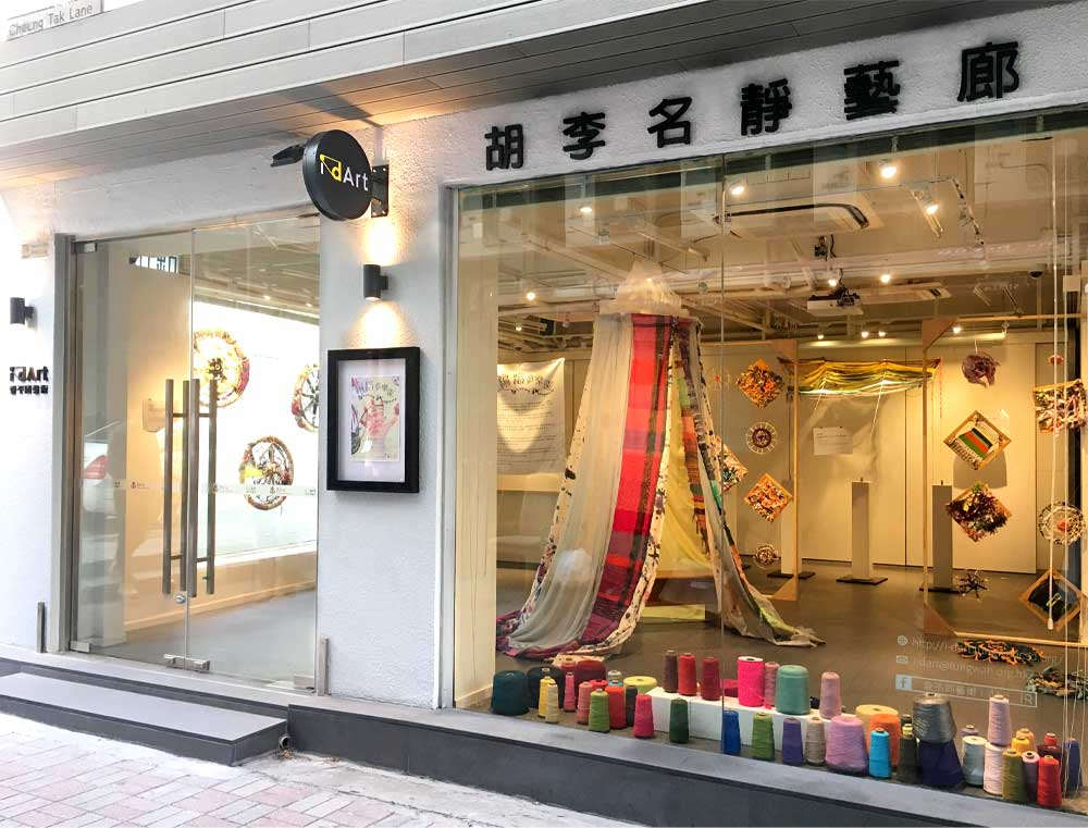 A glass storefront shows brightly colored spools of thread and several fiber arts pieces inside a street-level gallery.