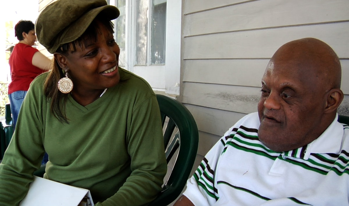 A black woman wearing a green shirt and cap smiles in conversation with a black man wearing a green and white striped shirt.