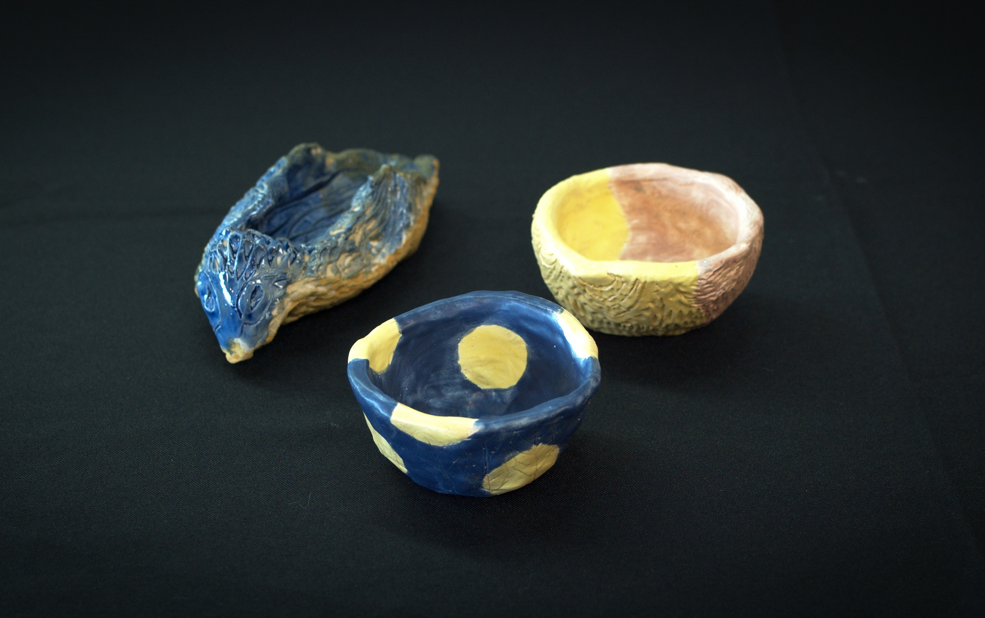 blue bird ceramic 3d spoon rest and two small bowls, one with yellow and pink polka dots and the other with navy and yellow polka dots