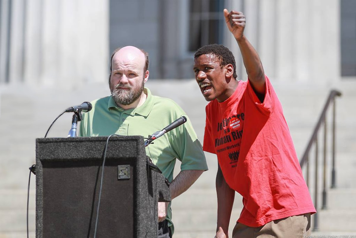 Max Barrows and Tracy Thresher stand at a podium with microphones in front of the Vermont State House during a rally about healthcare rights. Barrows is speaking and raising his arm in the air.