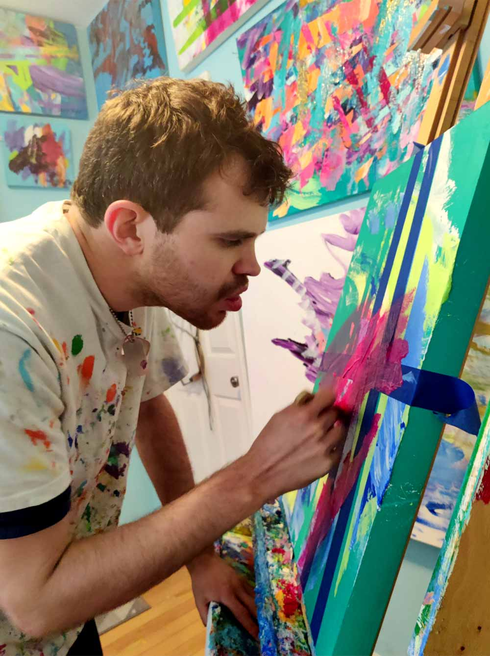 A young white man wearing a white t-shirt with paint stains and dog tag-style necklace looks closely at an abstract, colorful painting as he works on the piece.