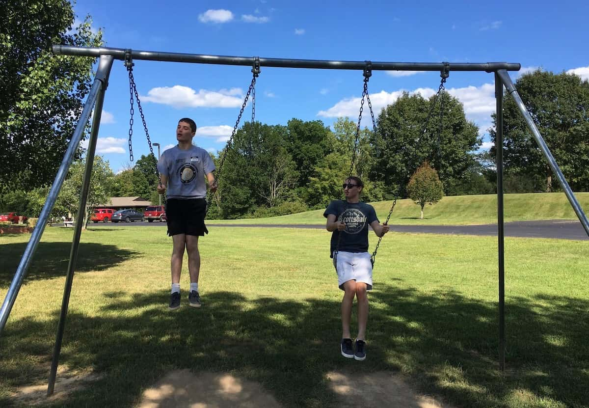 Dressed in shorts and sneakers, twin brothers Josh and Jacob swing on a metal swingset during a sunny day.