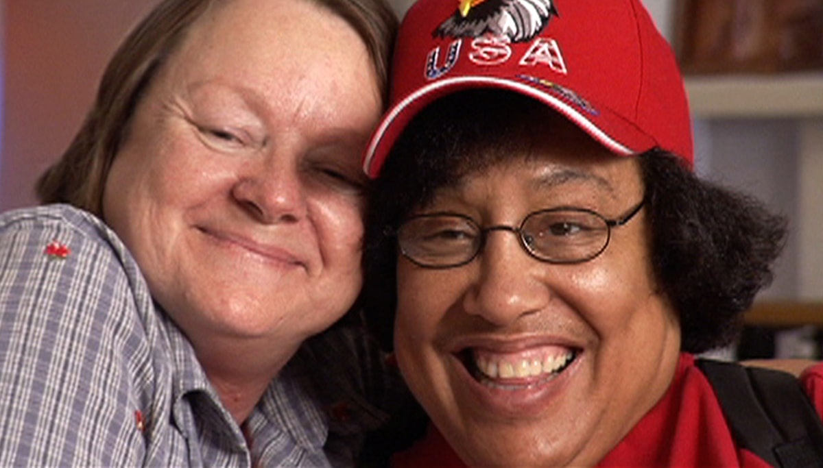 A white woman and a brown-skinned woman wearing wire-rimmed glasses and a red baseball cap both smile at the camera.