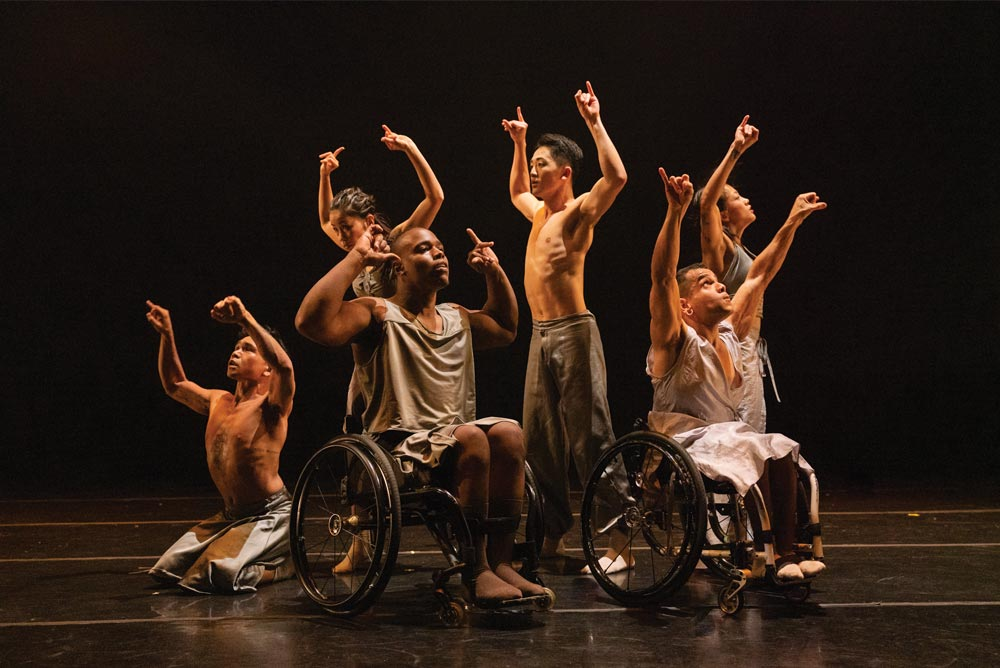 Dancers with and without visible disabilities sit, stand, and kneel in a clump on stage, facing different directions. The dancers raise their upper limbs into a gesture with closed fists as their thumbs and pinkies point out and upwards. The dancers wear silver, flowing costumes.