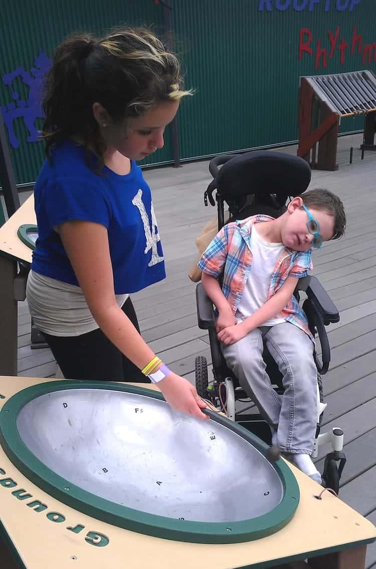 Adolescent sister and elementary-age brother who's seated in a wheelchair together on a playground deck looking at and tapping on a big metal disk that's part of a sound-making educational experience.
