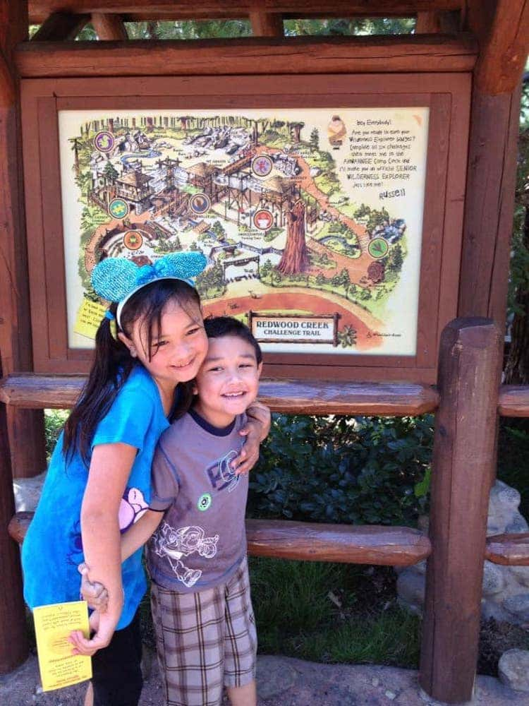 Elementary-age sister with her younger brother standing in front of a map of a challenge trail in a park. They're embracing and smiling.