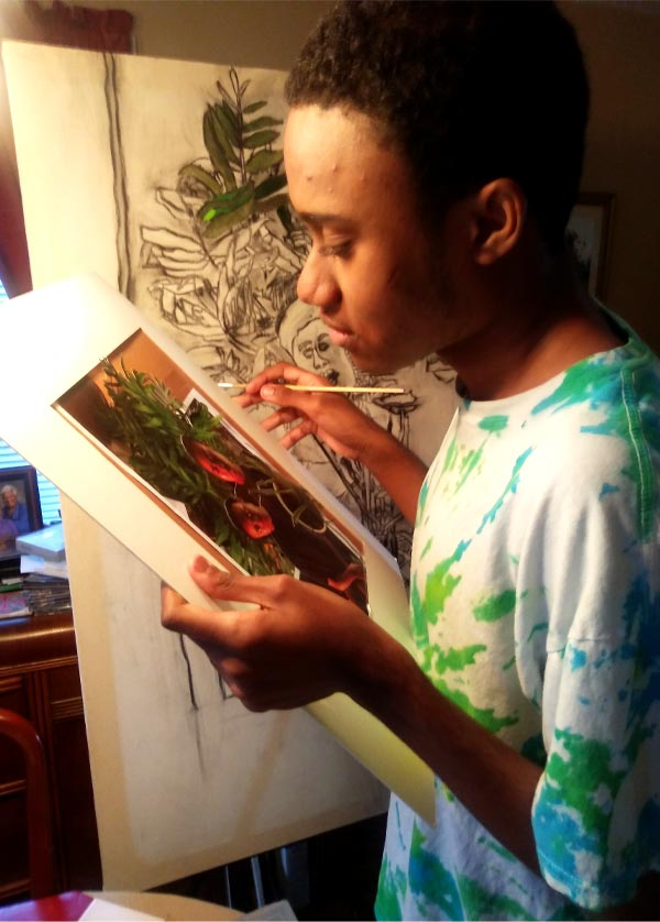 An artist holding a paintbrush studies a photo of himself and his mother standing in front of a large green plant.