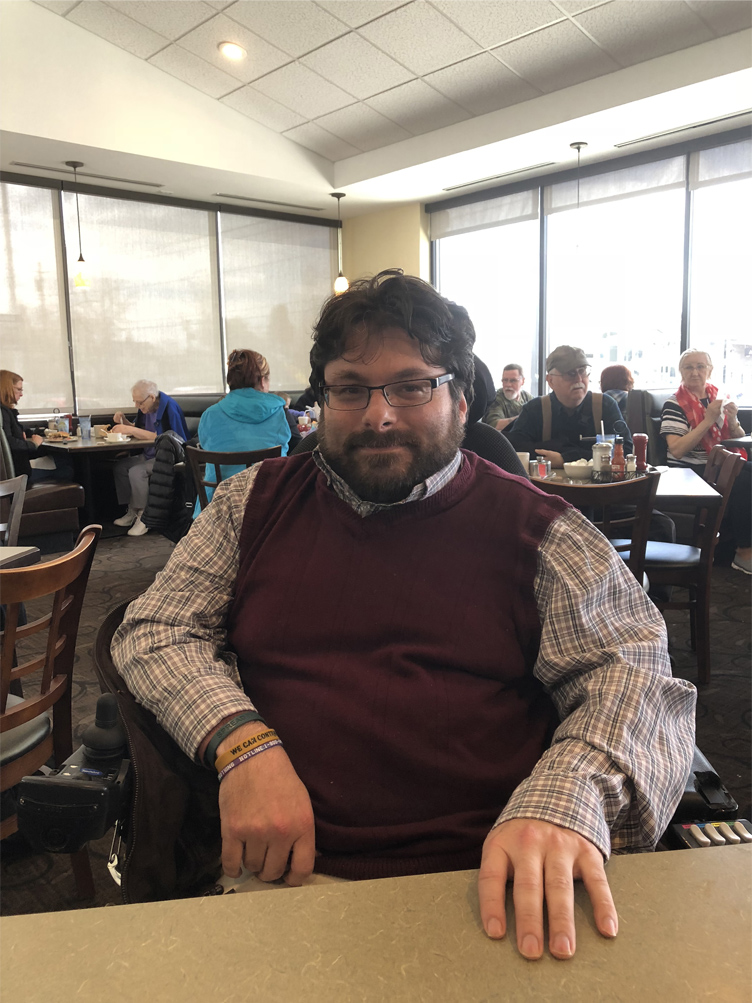 Samuel R. Mattle, Founder of the Center for Self Advocacy, sits at a table wearing glasses, a checked shirt, and vest.