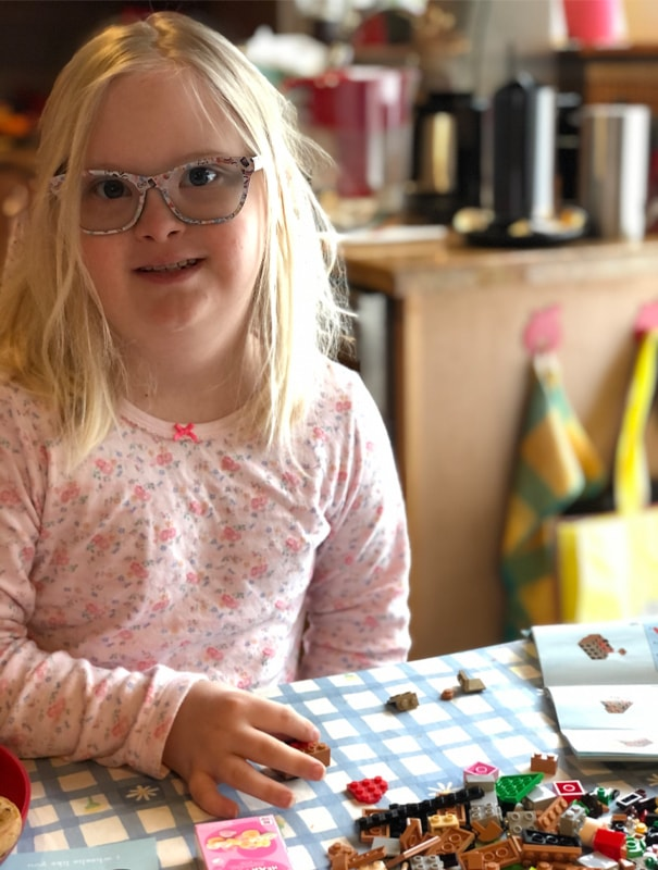 A young child with blonde hair, large gray plastic glasses and wearing a pink top with flowers and a pink bow smiles at the camera. She's holding a small building block and there are others on the blue-checked table.