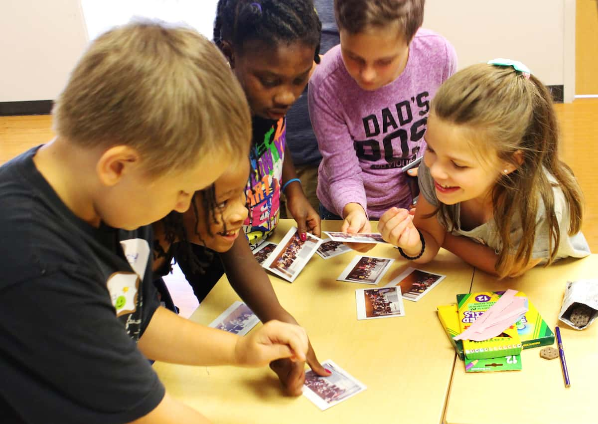 Five young children crowd around activity cards as they participate in a workshop for siblings. A couple of the children smile excitedly as one points to a card.