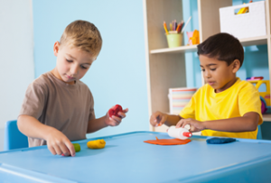 A photo of two boys approximately four to five years old playing with modeling clay in a classroom setting