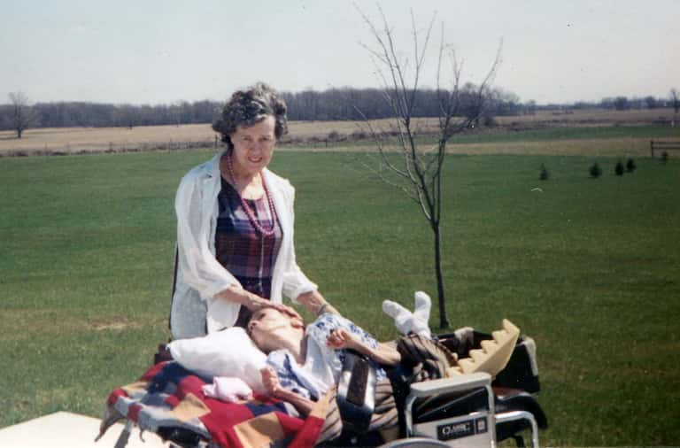 Gayle sits in a wheelchair outside, looking up toward her mother, who is smiling slightly. Behind them is a green, rural field and a young tree.