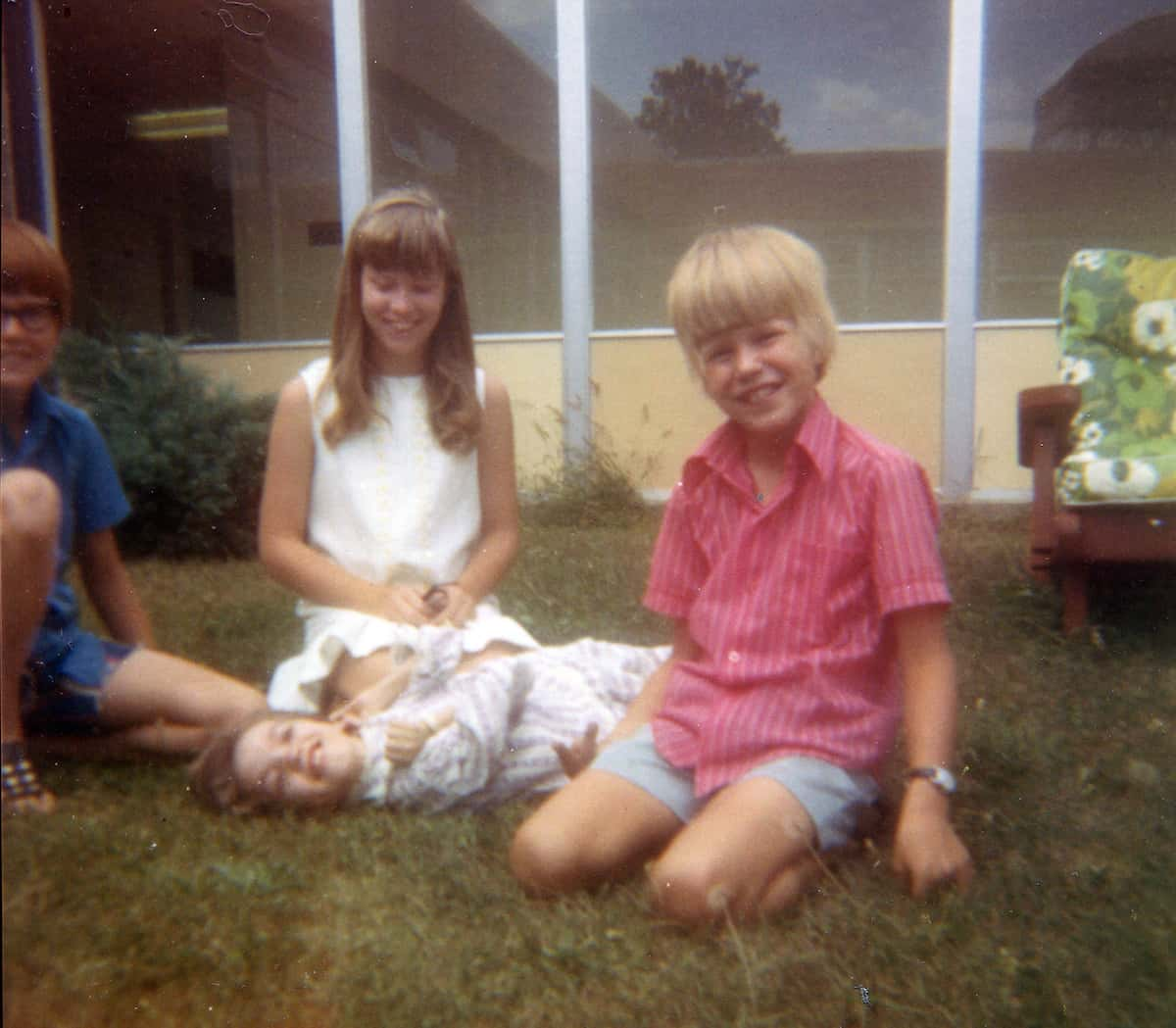 The four Smith siblings, all smiling, sit in the grass outside Gayle's residential facility. Gayle is lying on a blanket in the grass.