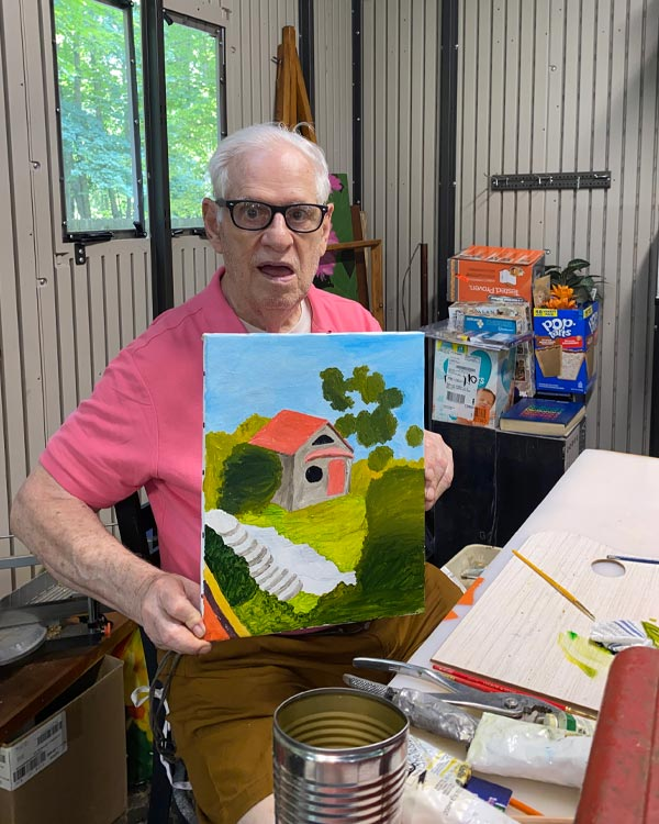 An elderly white man in black glasses and a pink shirt sits at his studio table, holding up a painting of a landscape with a house. Around him are art supplies, a box of breakfast pastries, and other pantry items and supplies.